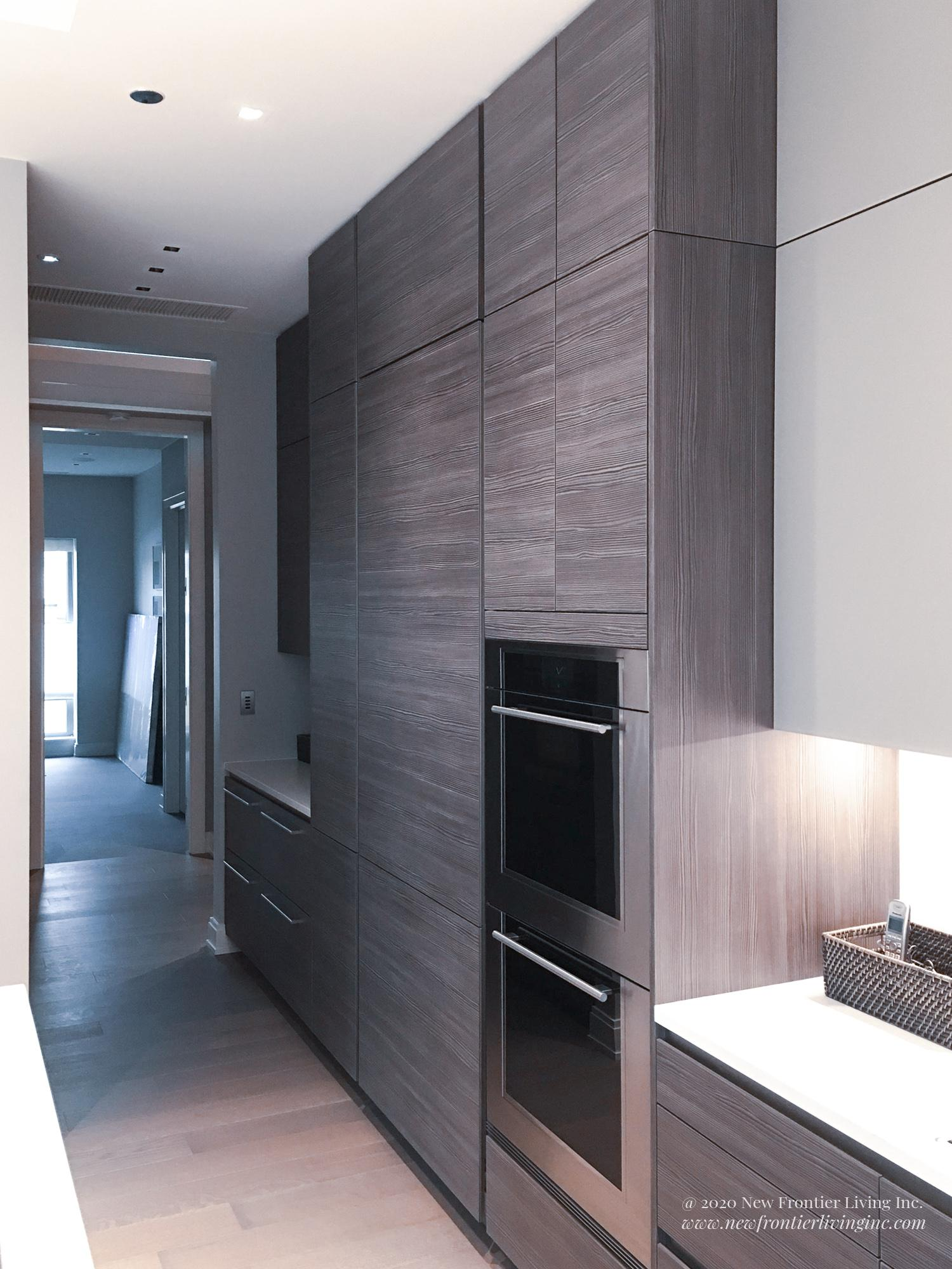 Dark kitchen paneling cabinetry and ovens