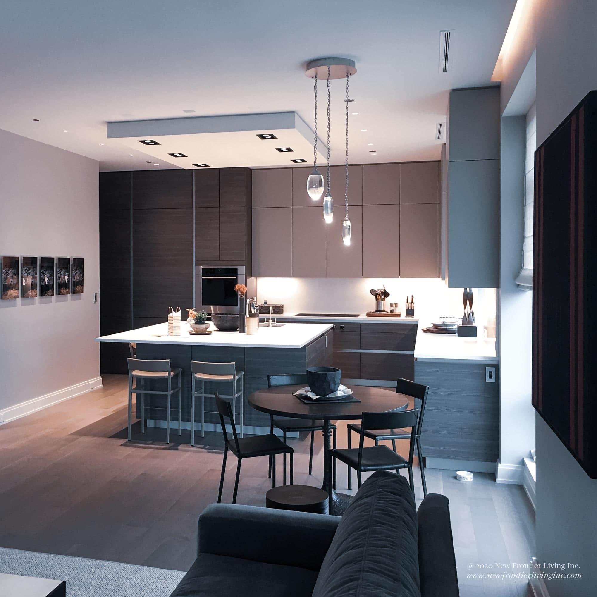Black kitchen cabinetry with white countertop and square kitchen island long view