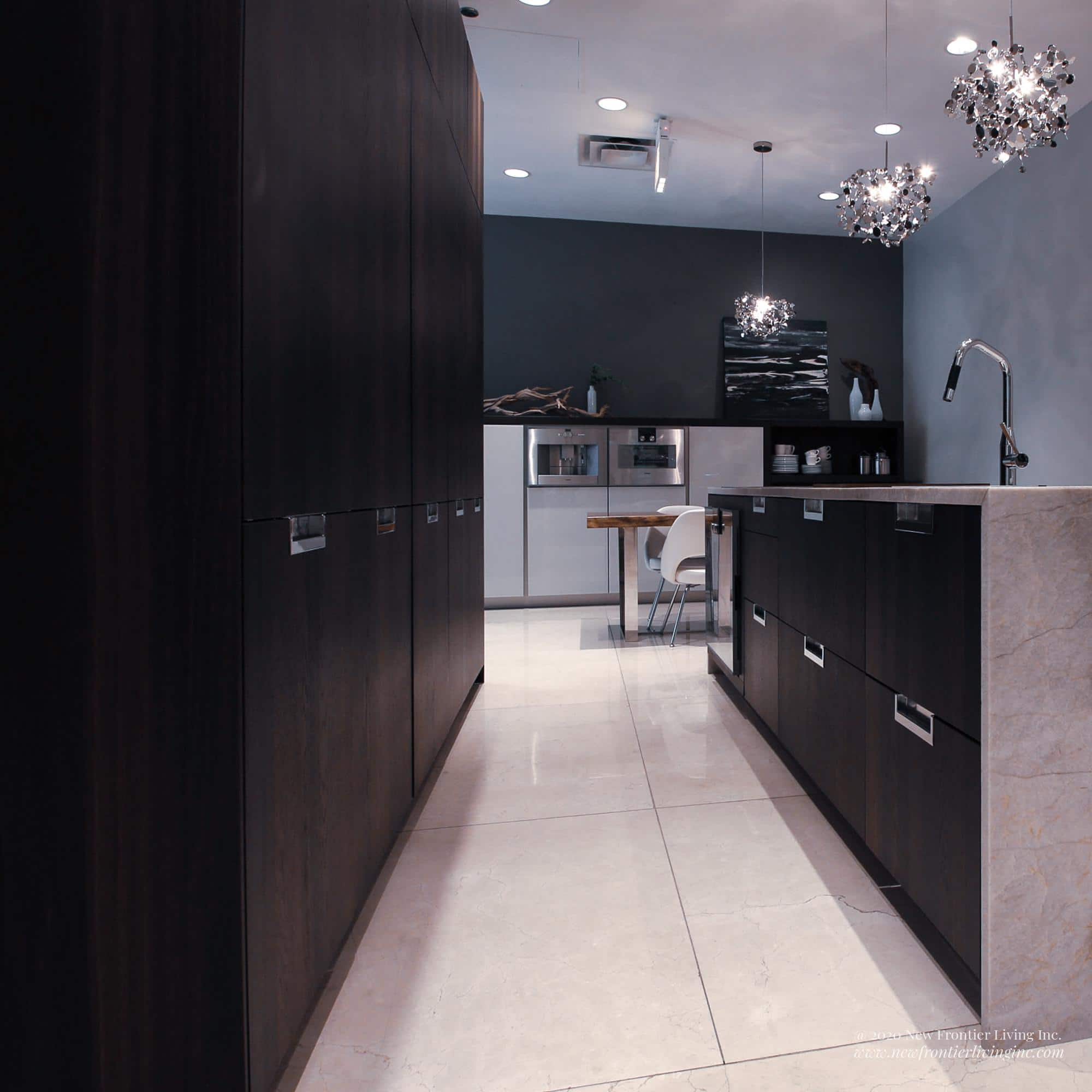 Tall black kitchen cabinets and an island with cream waterfall countertop