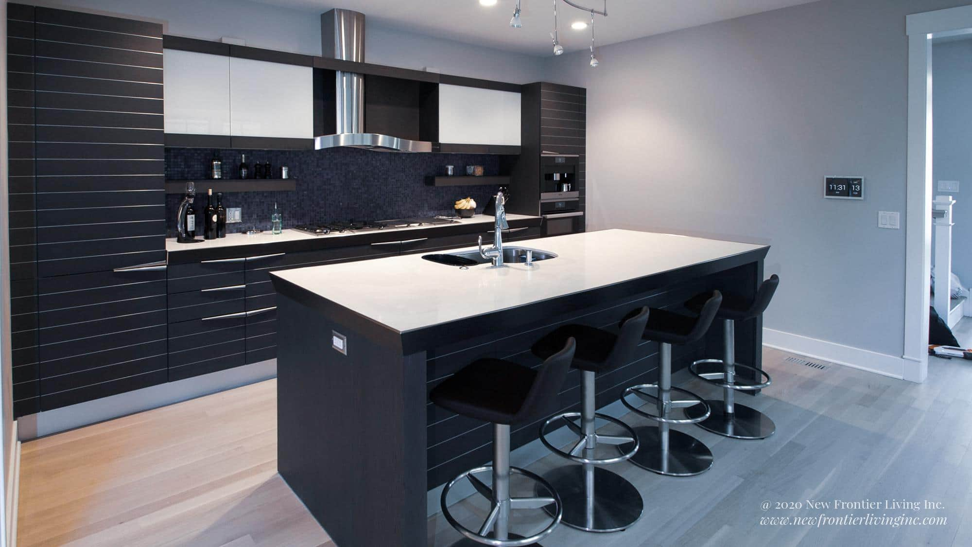 Black kitchen with light spaces, black kitchen island with white countertop and four bar stools