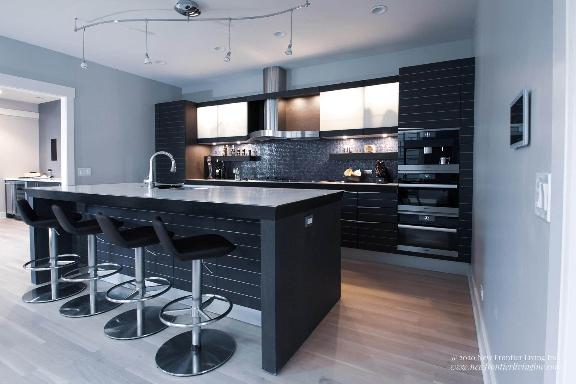 Black kitchen with light spaces, black kitchen island, sliding glass upper cabinets