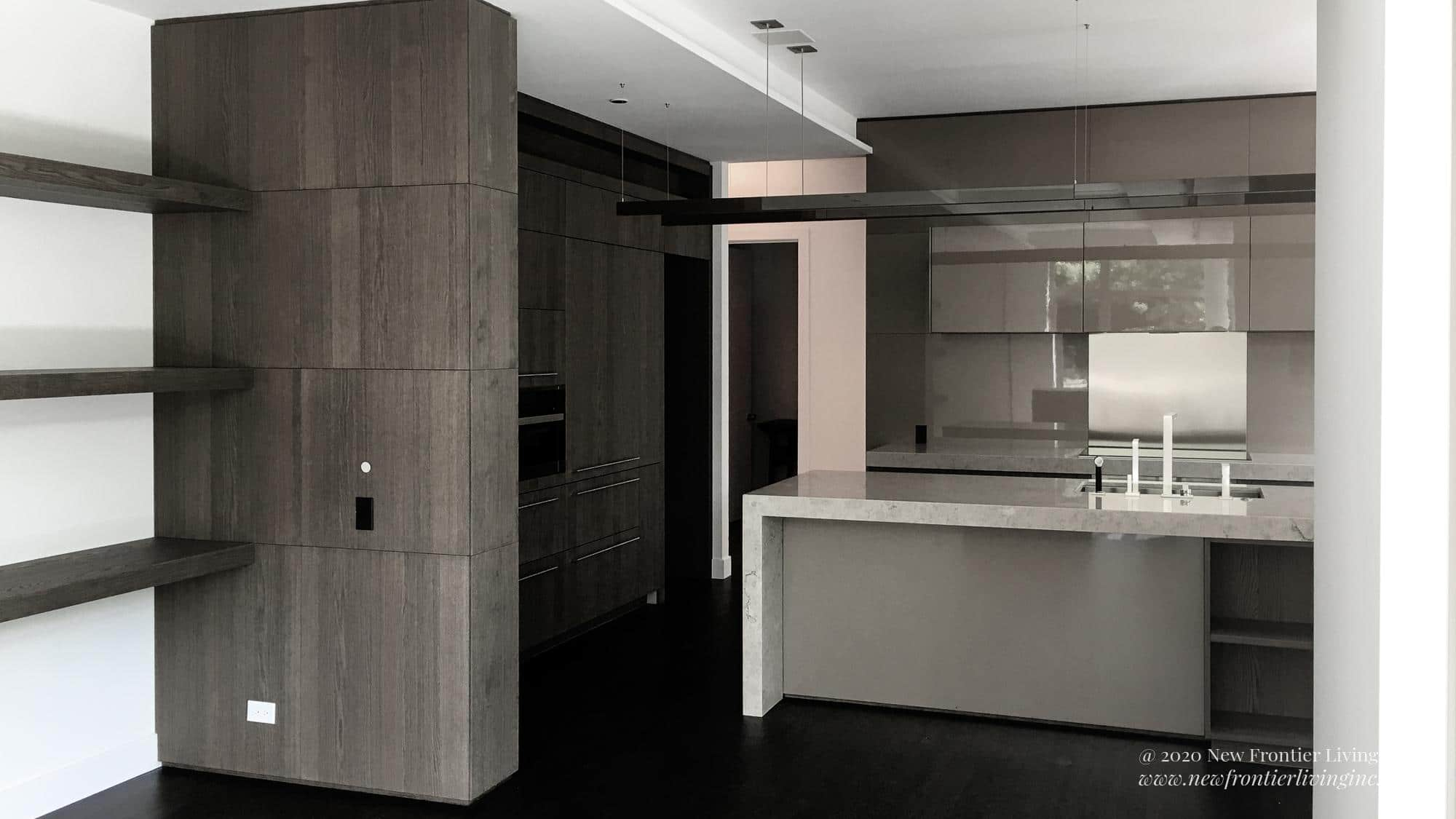 Gray and white waterfall kitchen island with modern sinks and wall cabinetry, side shelves on the wall to the left
