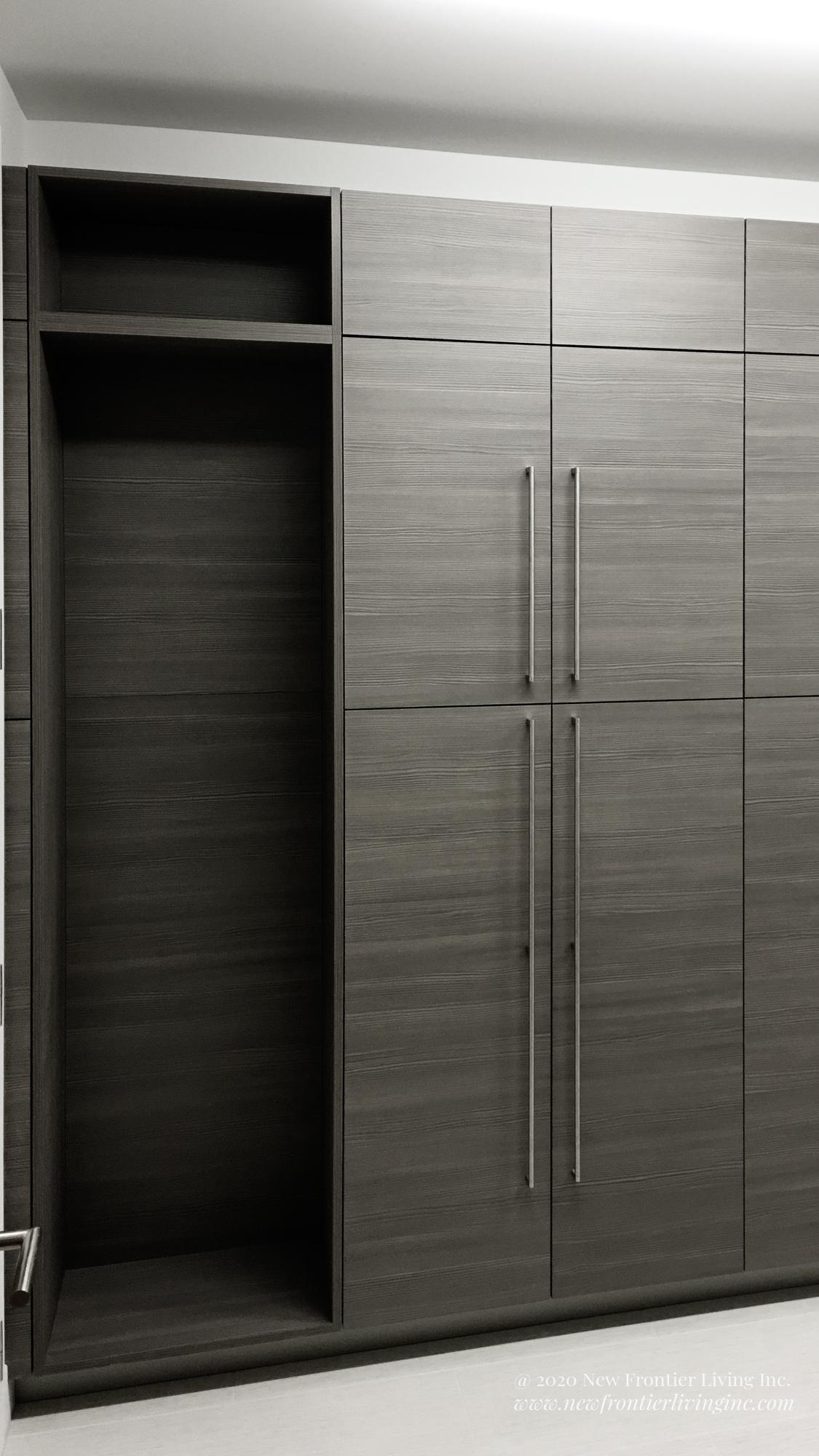 Large dark gray wooden cabinetry covering entire wall with silver handles