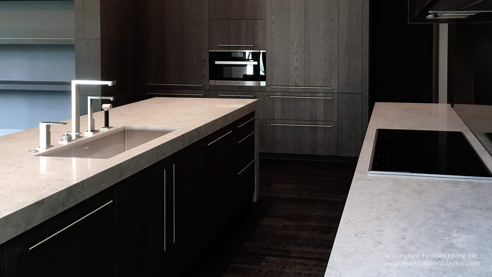 White countertop kitchen island with sink to the left and wall countertop with cooktop to the right