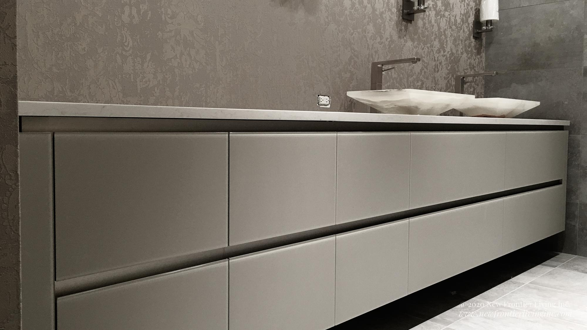 Light brown wall cabinetry without handles and two sinks, four lights above on the wall