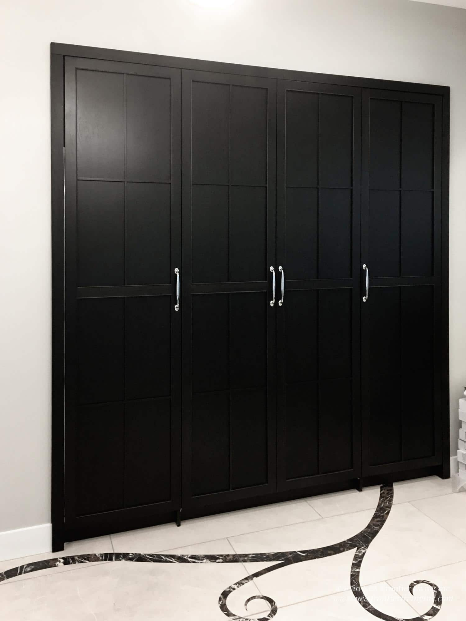 Black tall kitchen pantry with silver handles