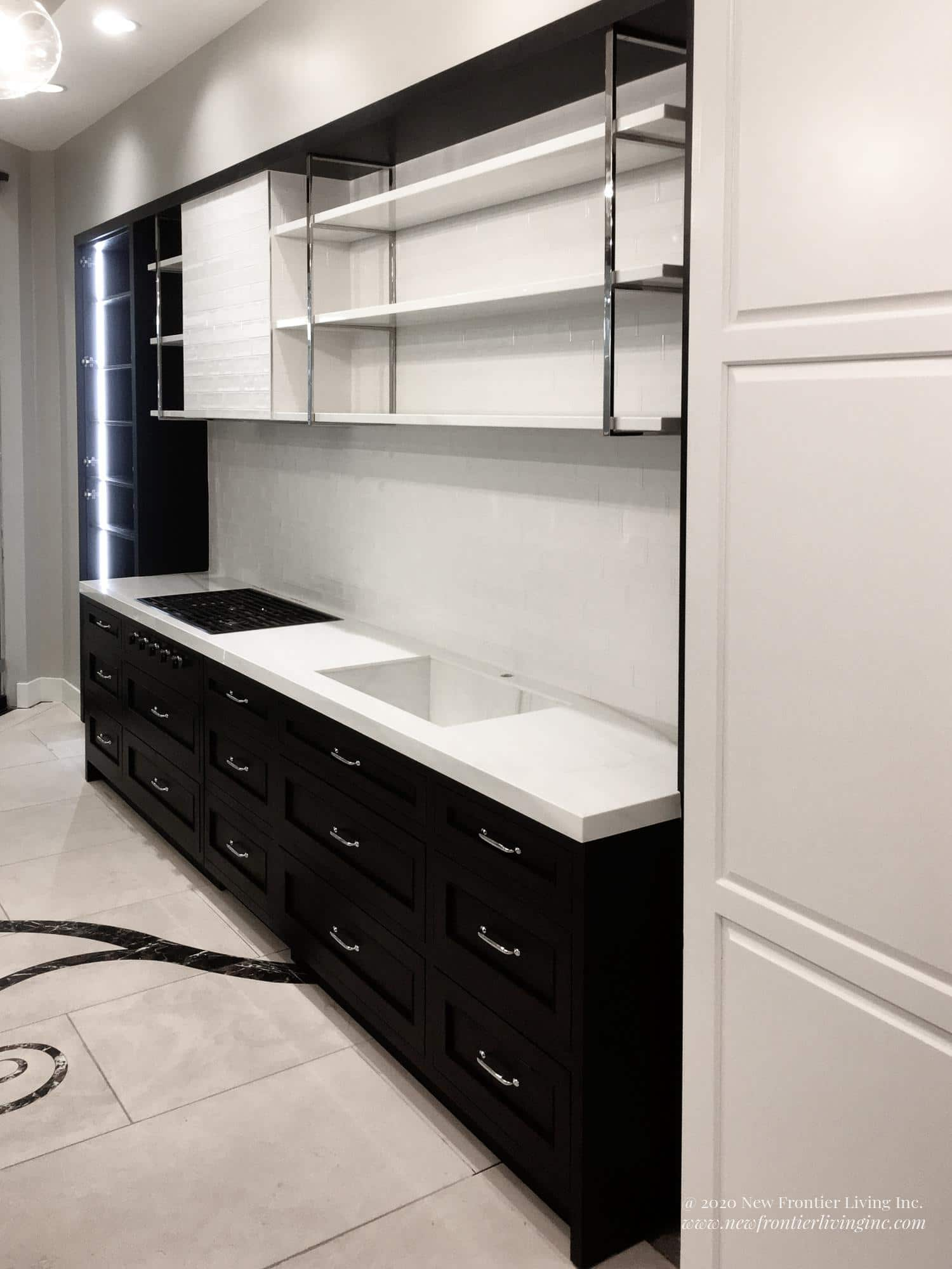 Black kitchen cabinets with silver handles and white countertop, white floor with black design