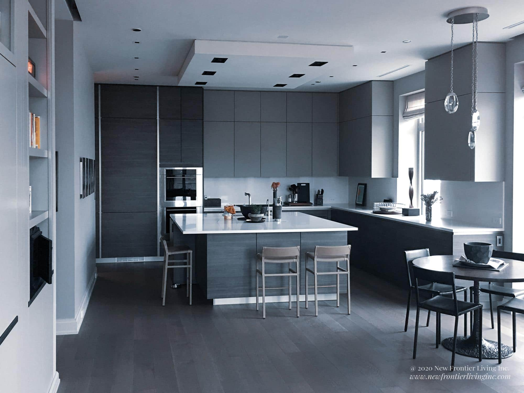 Black kitchen with square island and stools, round extra table on the right