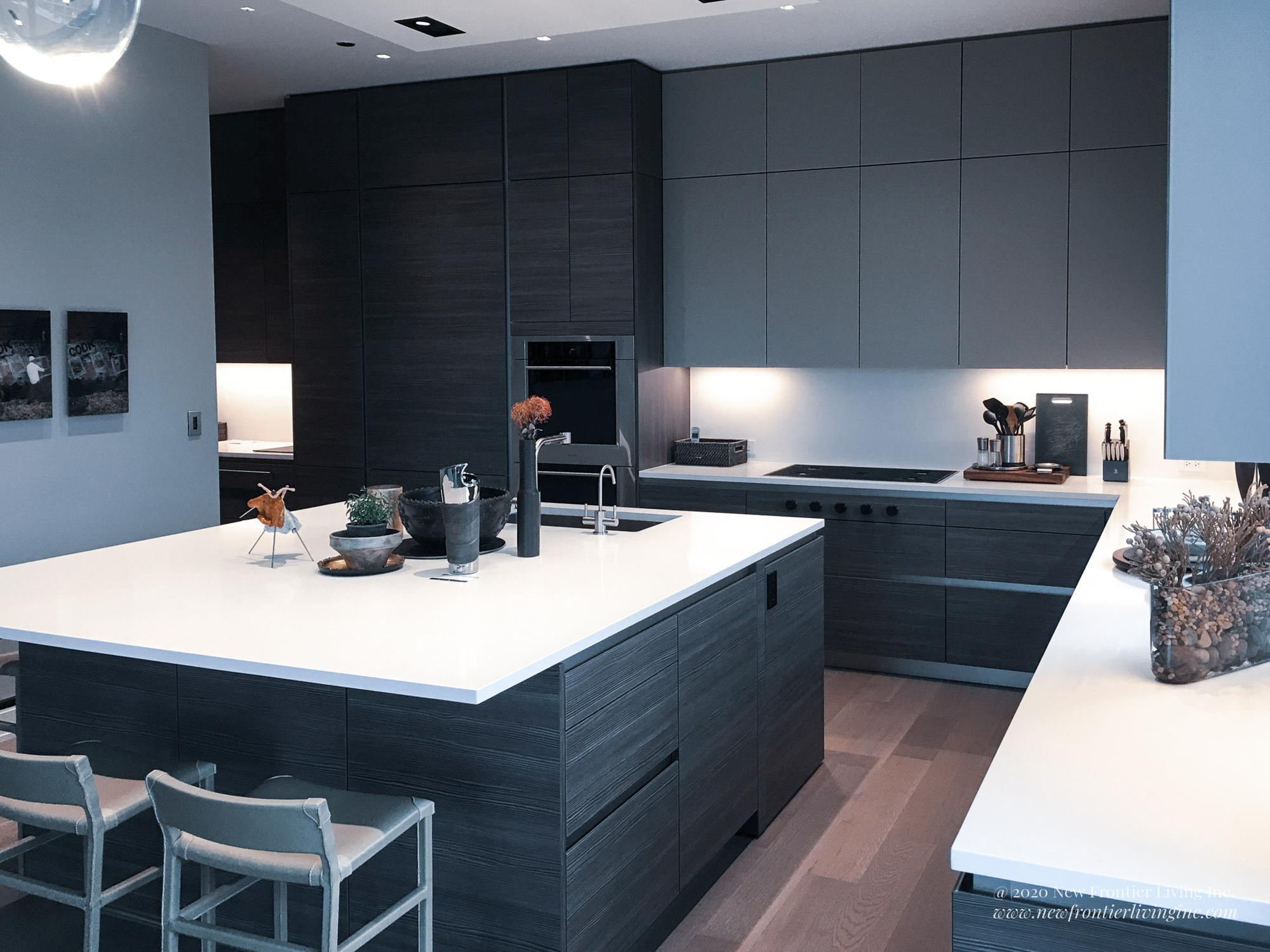 Black kitchen cabinetry with white countertop and square kitchen island