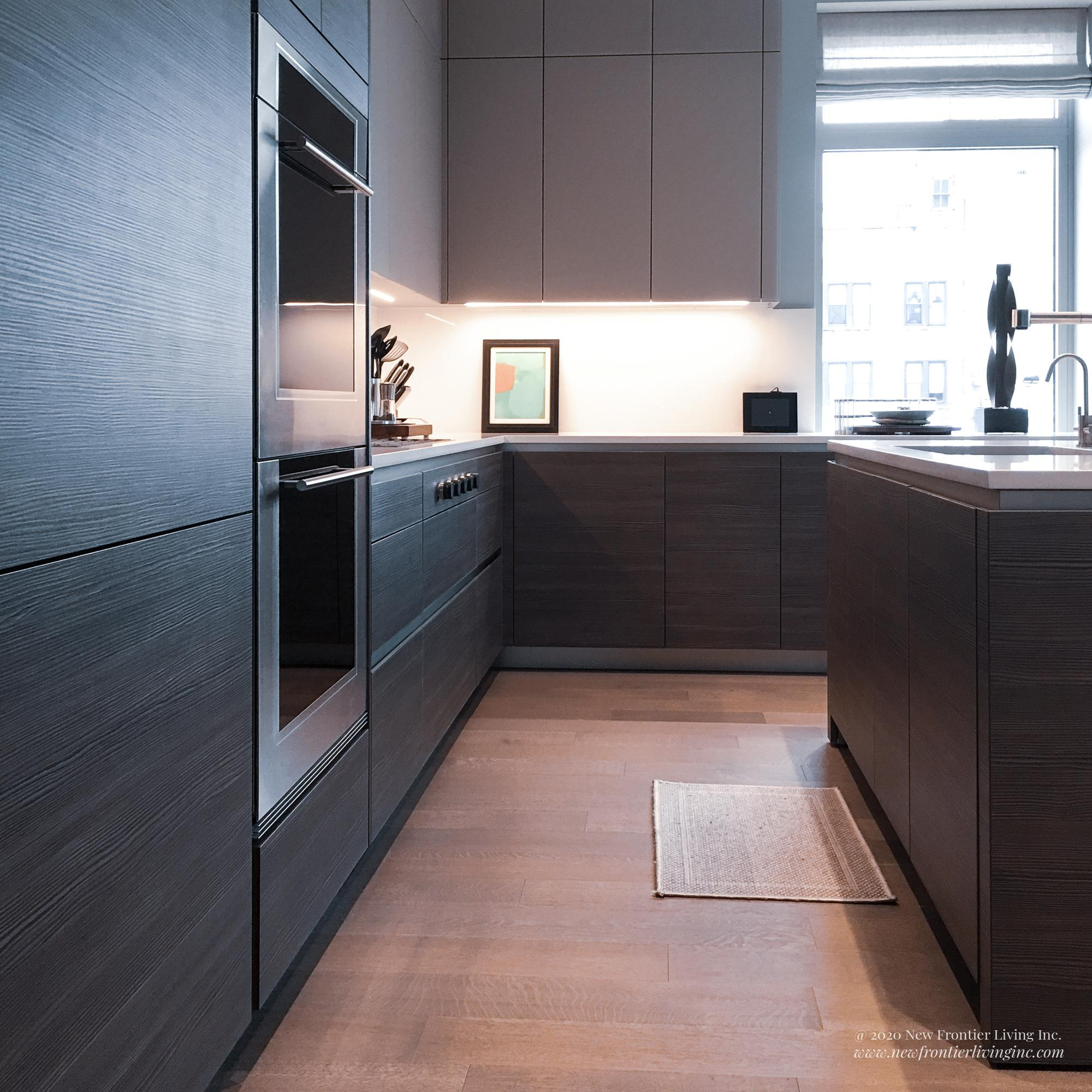 Black kitchen bottom cabinetry without handles with wooden floor