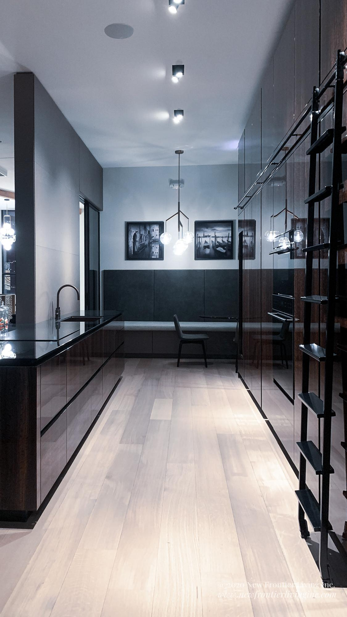 Black and Brown glossy kitchen with black countertop and light wooden floor, sliding ladder on the right