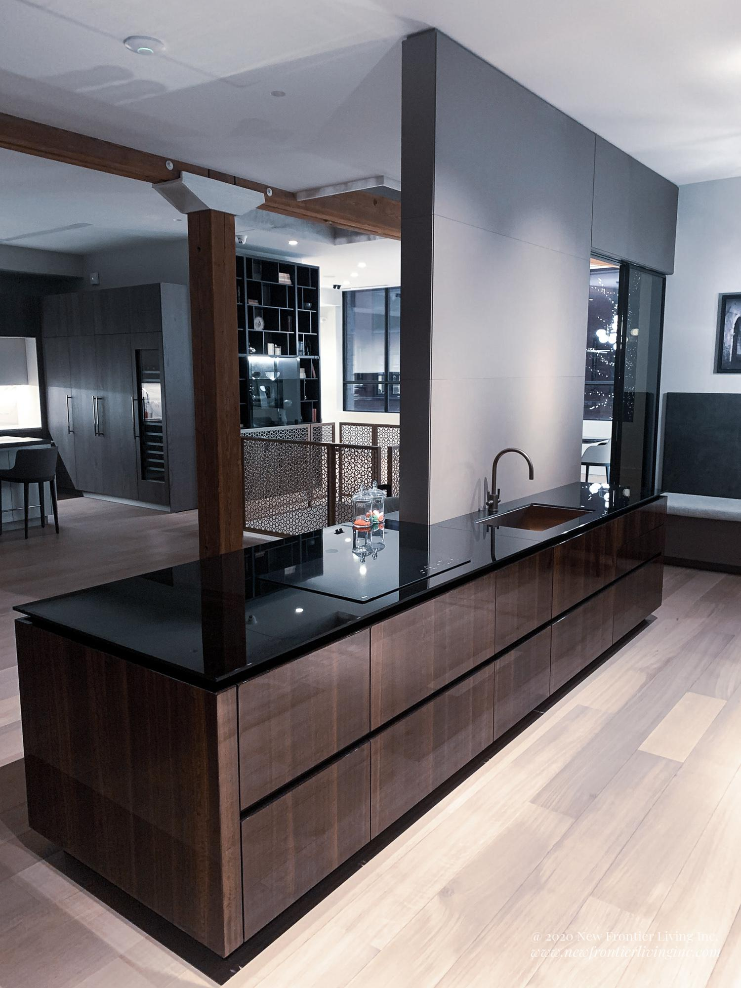Black and Brown glossy kitchen with black countertop and light wooden floor
