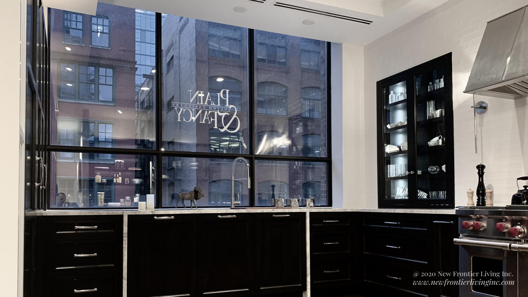 Traditional black kitchen with gray countertop, window to the city