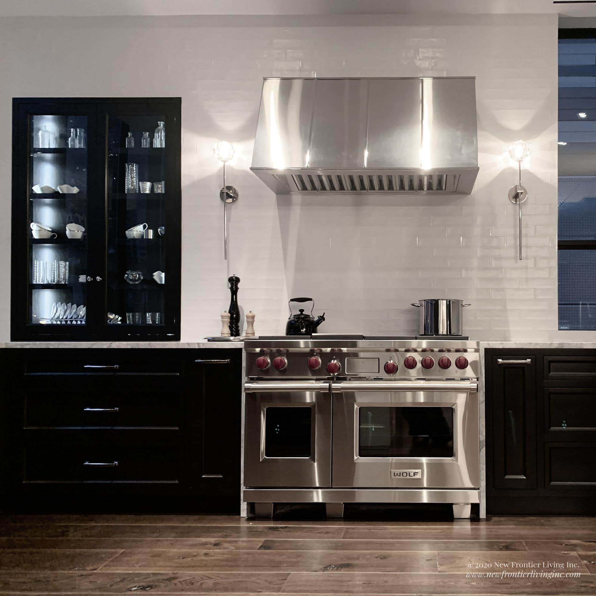 Traditional black kitchen with gray countertop and stainless steel hood and cooktop and oven with red knobs