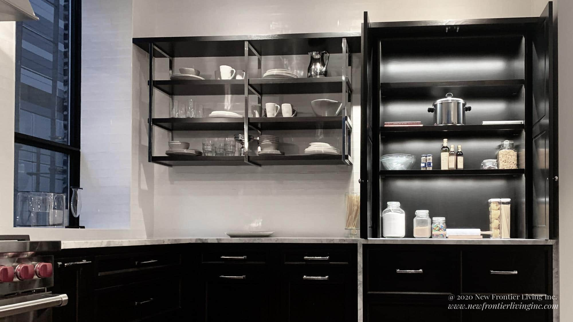 Traditional black kitchen with gray countertop, open shelves with dishes and food containers