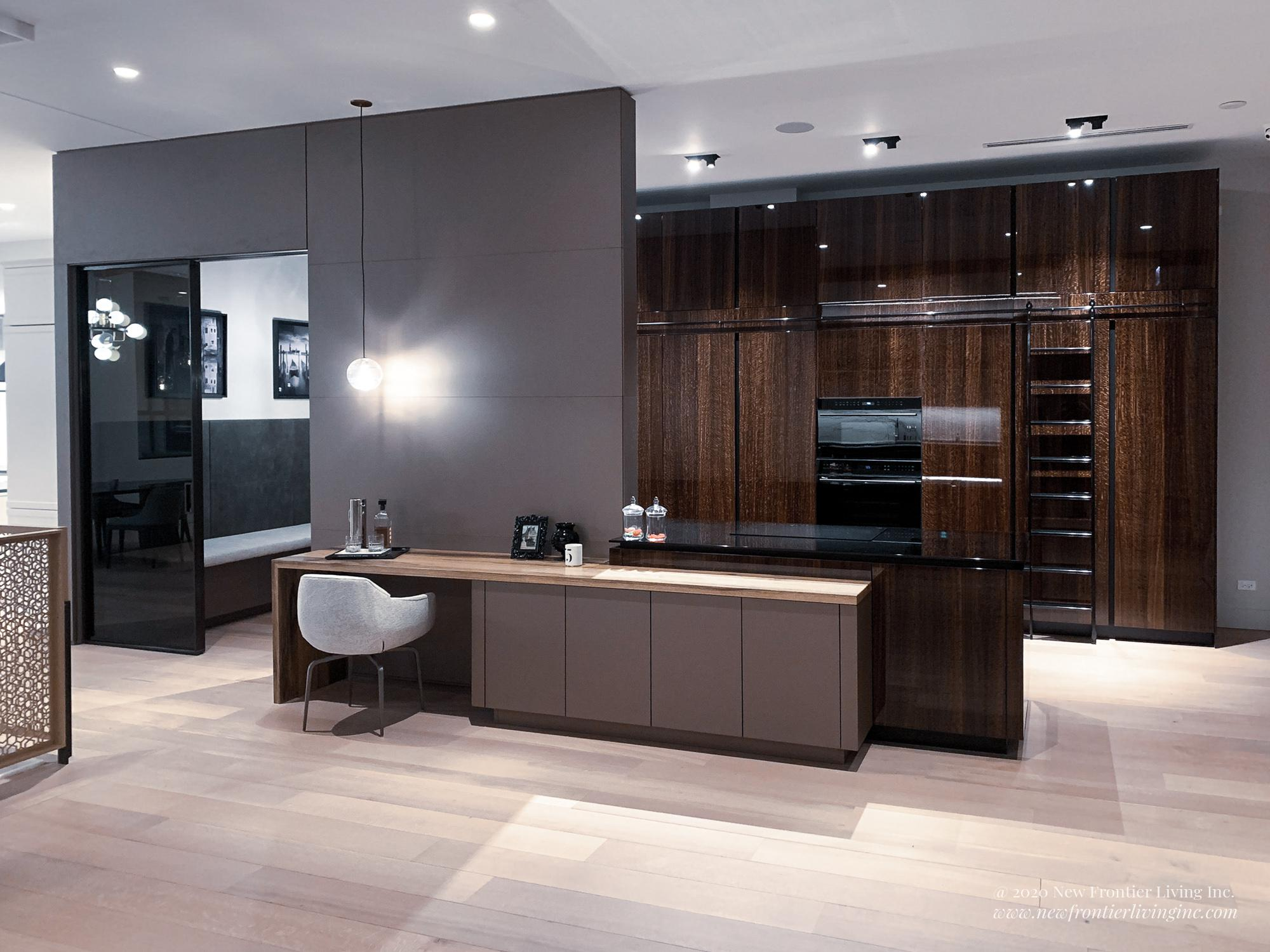 Brown glossy kitchen with a sliding ladder, chair and desk on other side