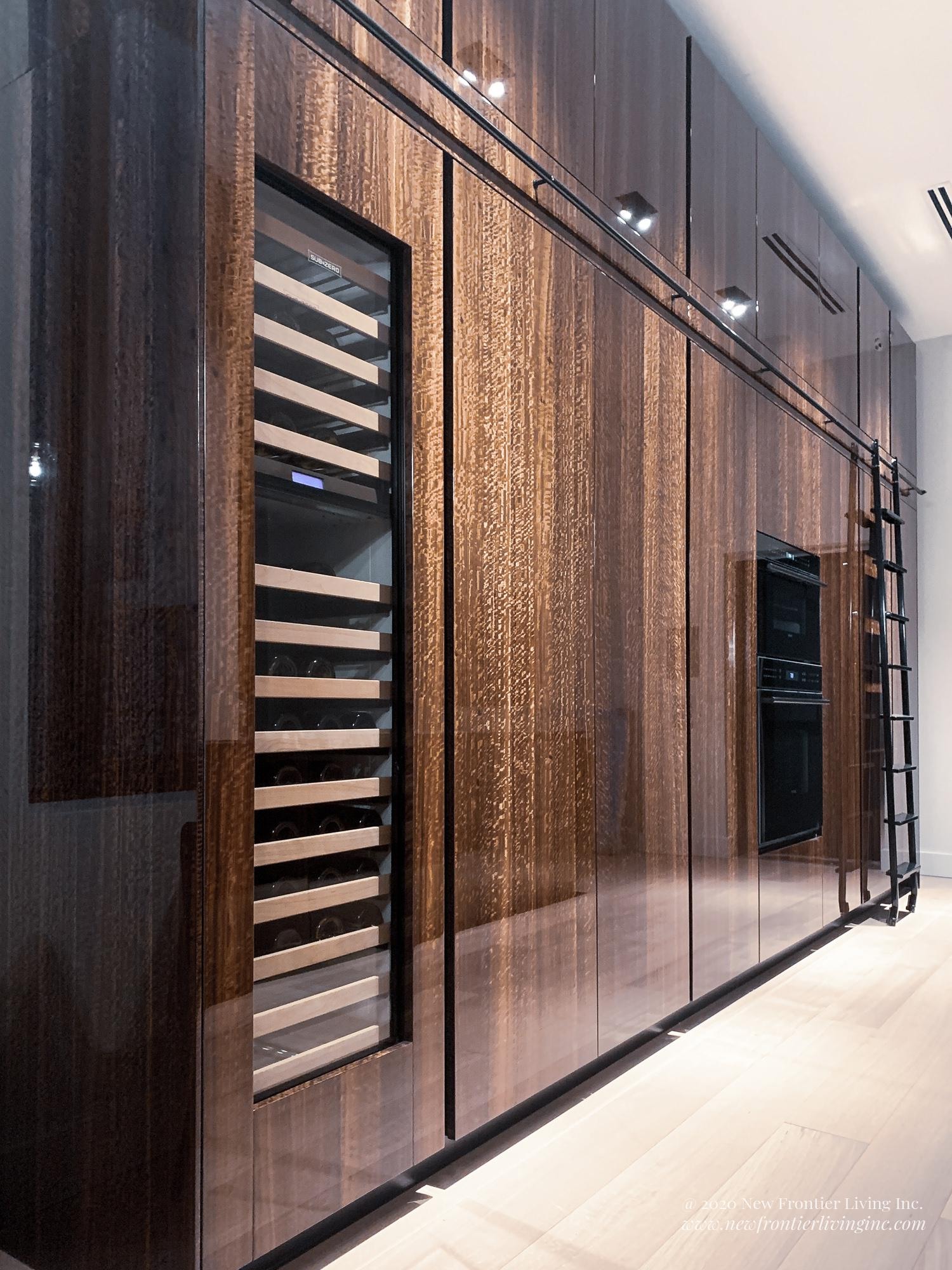Brown glossy tall kitchen cabinets and wine cooler
