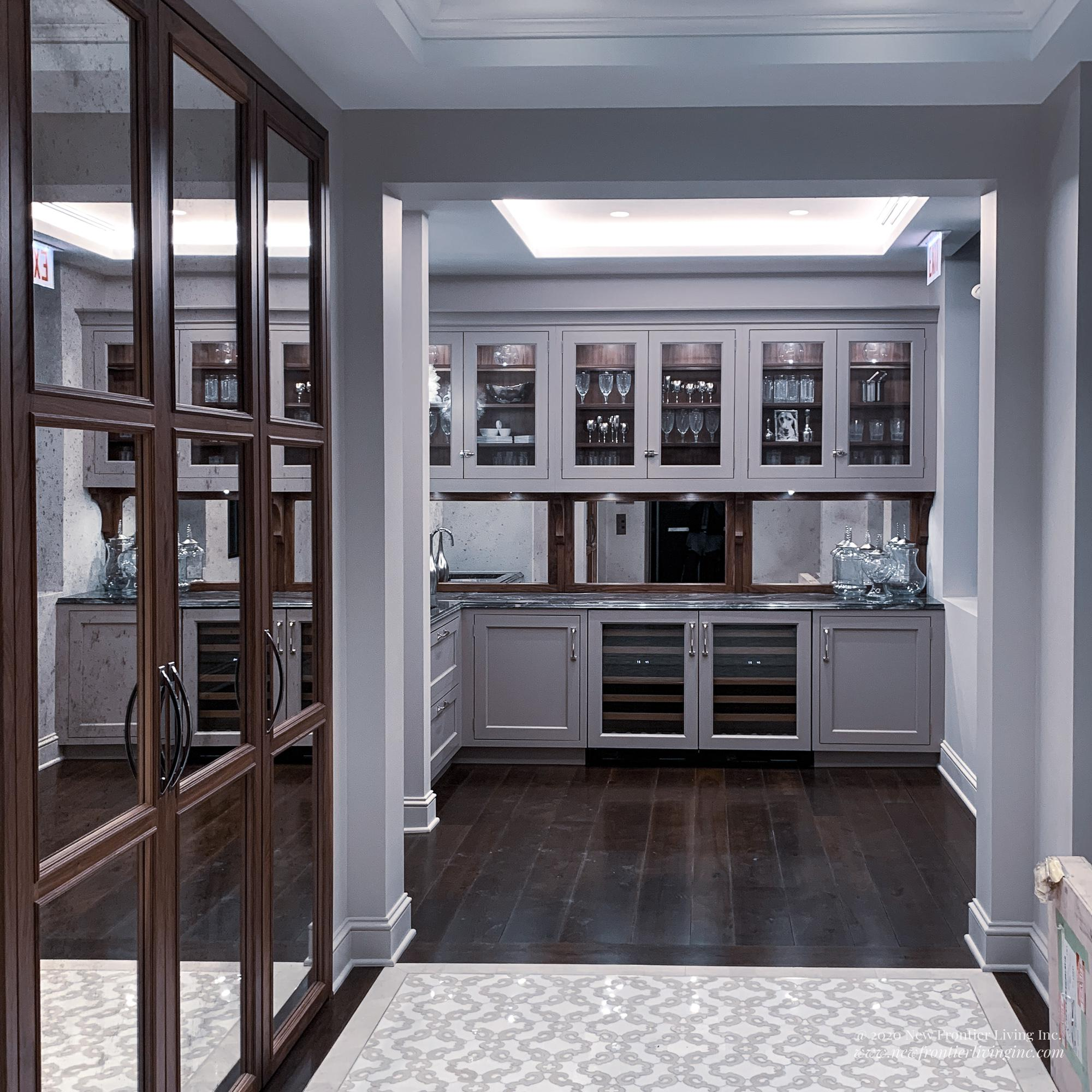 Lavender traditional kitchen cabinetry and upper glass cabinets, tall mirror pantries on the left, mirror backsplash