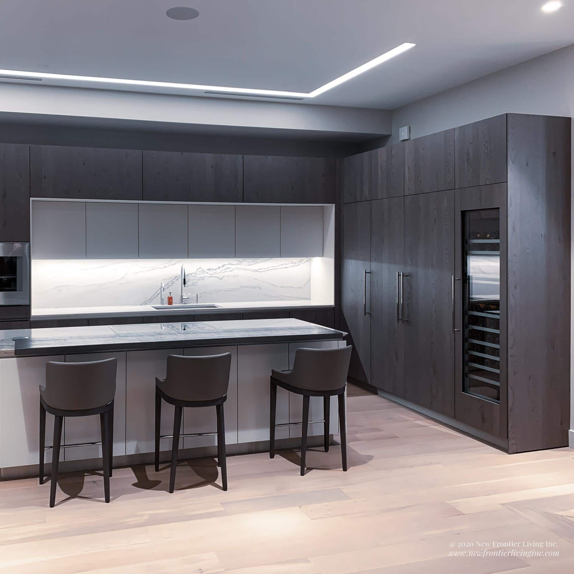 Black kitchen cabinetry and white island, large storage cabinets and wine cooler on the right