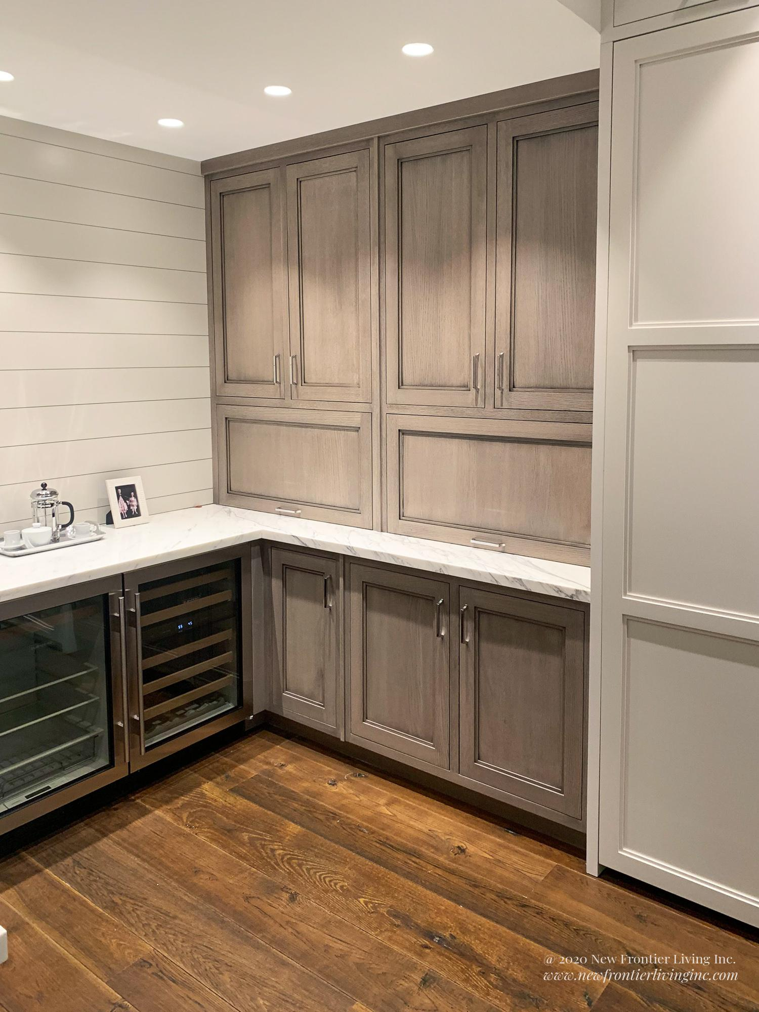 Matte peach kitchen cabinetry and white countertop, wine coolers on the bottom