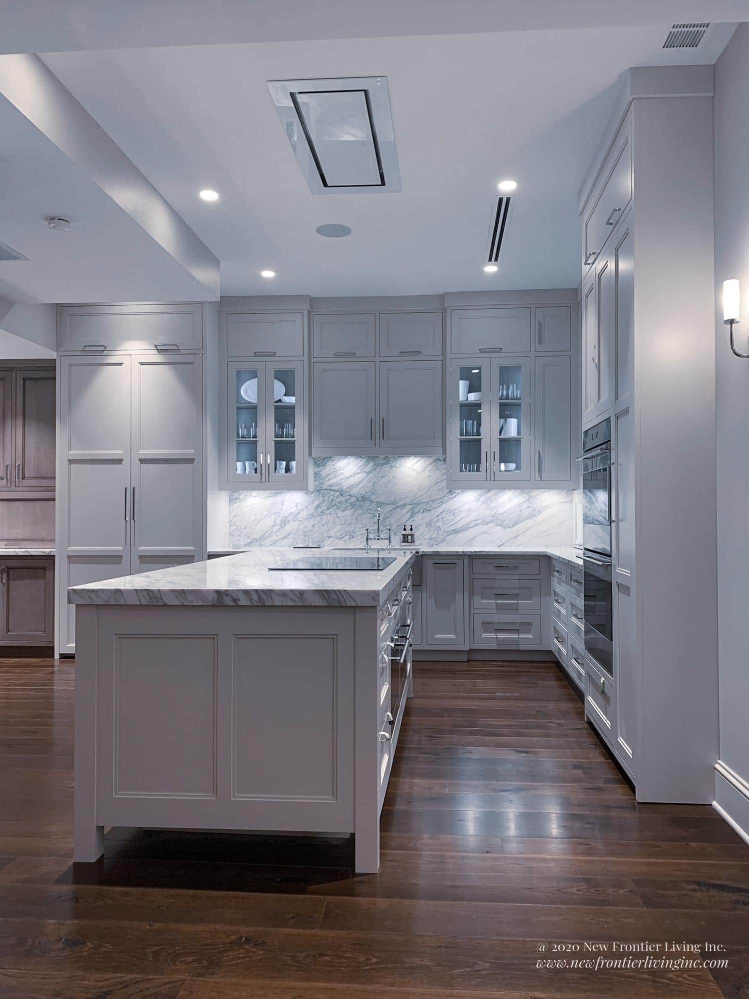 Pure white kitchen cabinetry and an island with semi-glass upper cabinets and silver handles