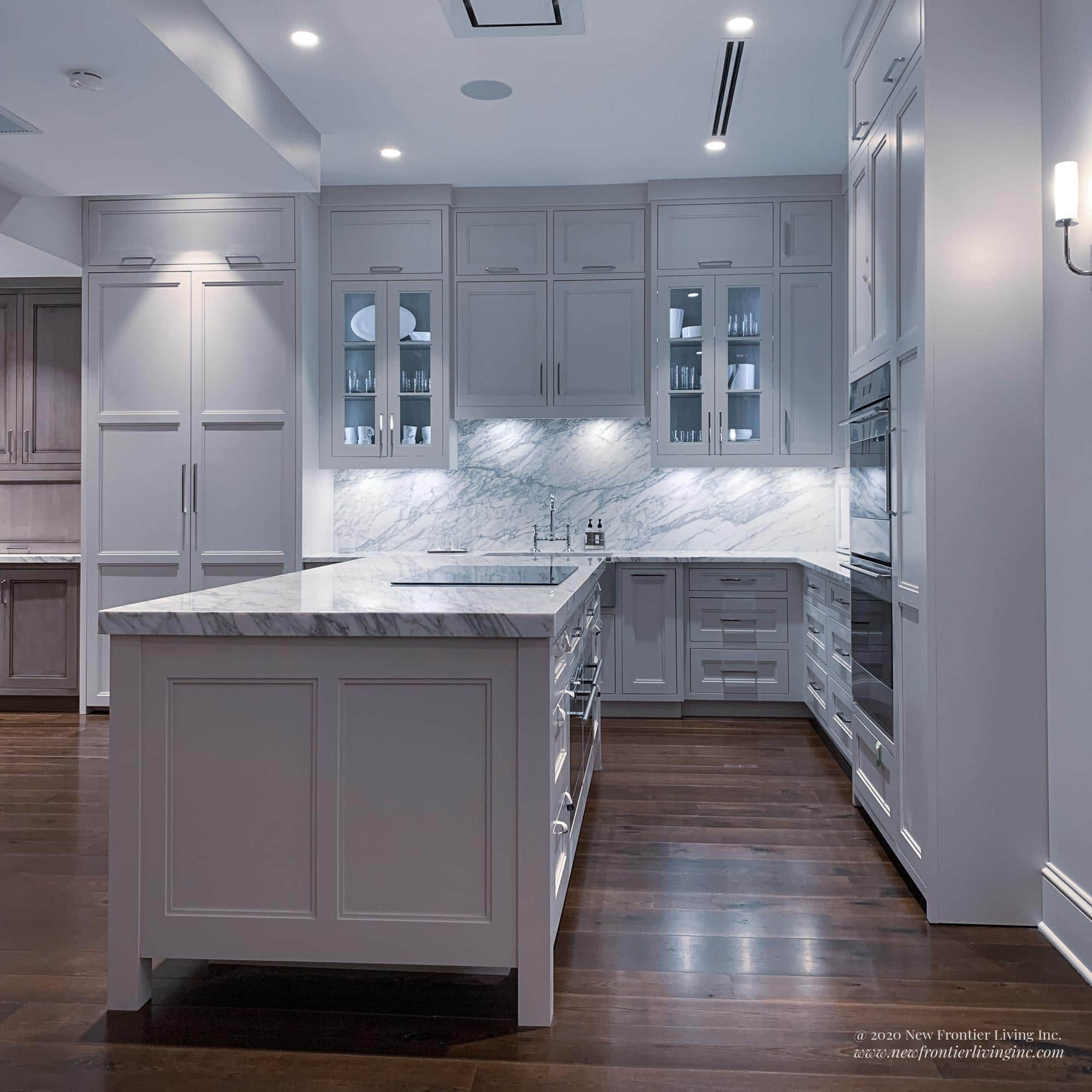 Pure white kitchen island and semi-glass upper cabinetry on the wall