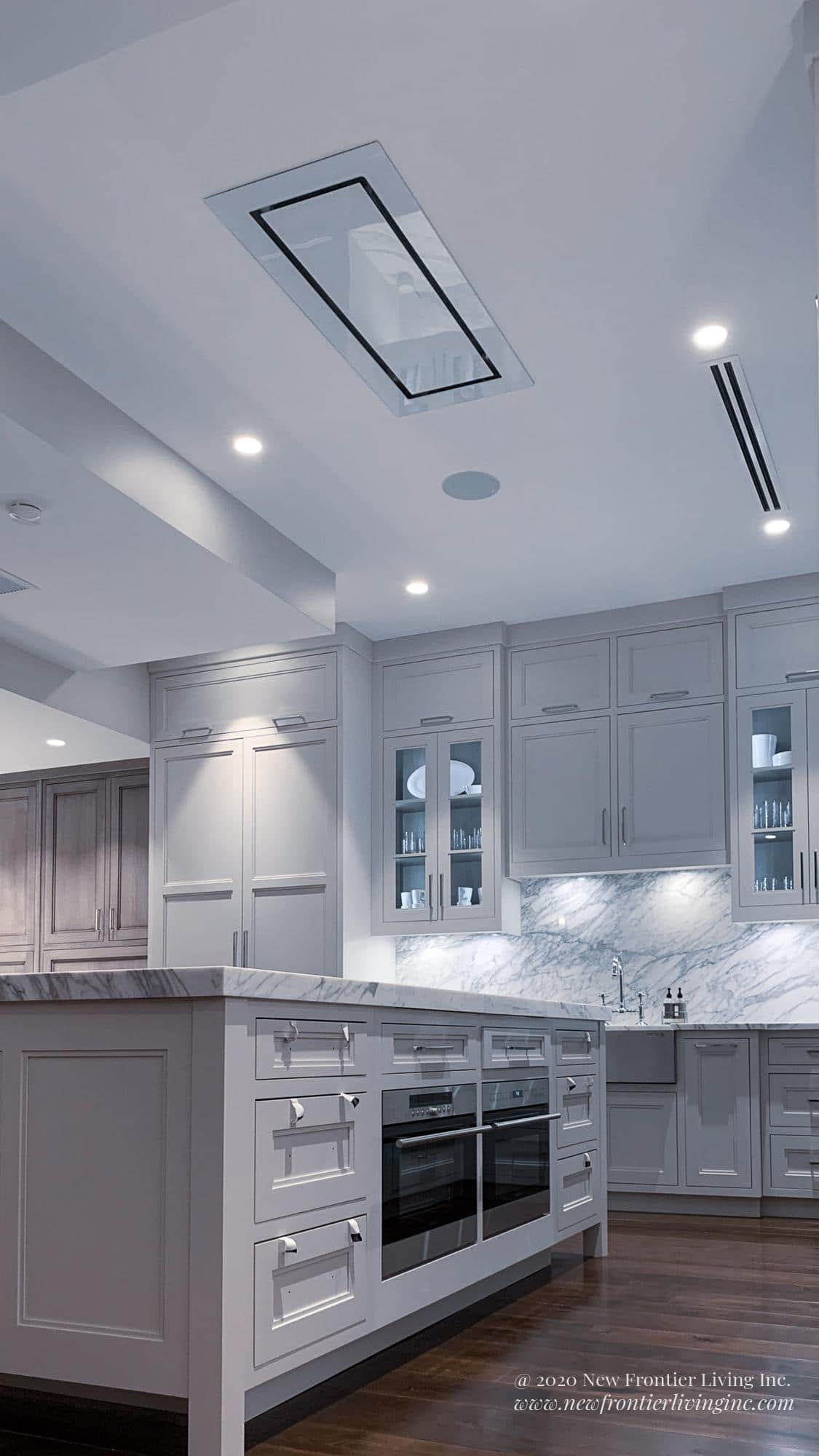 Pure white kitchen island with an oven and microwave at the bottom cabinets