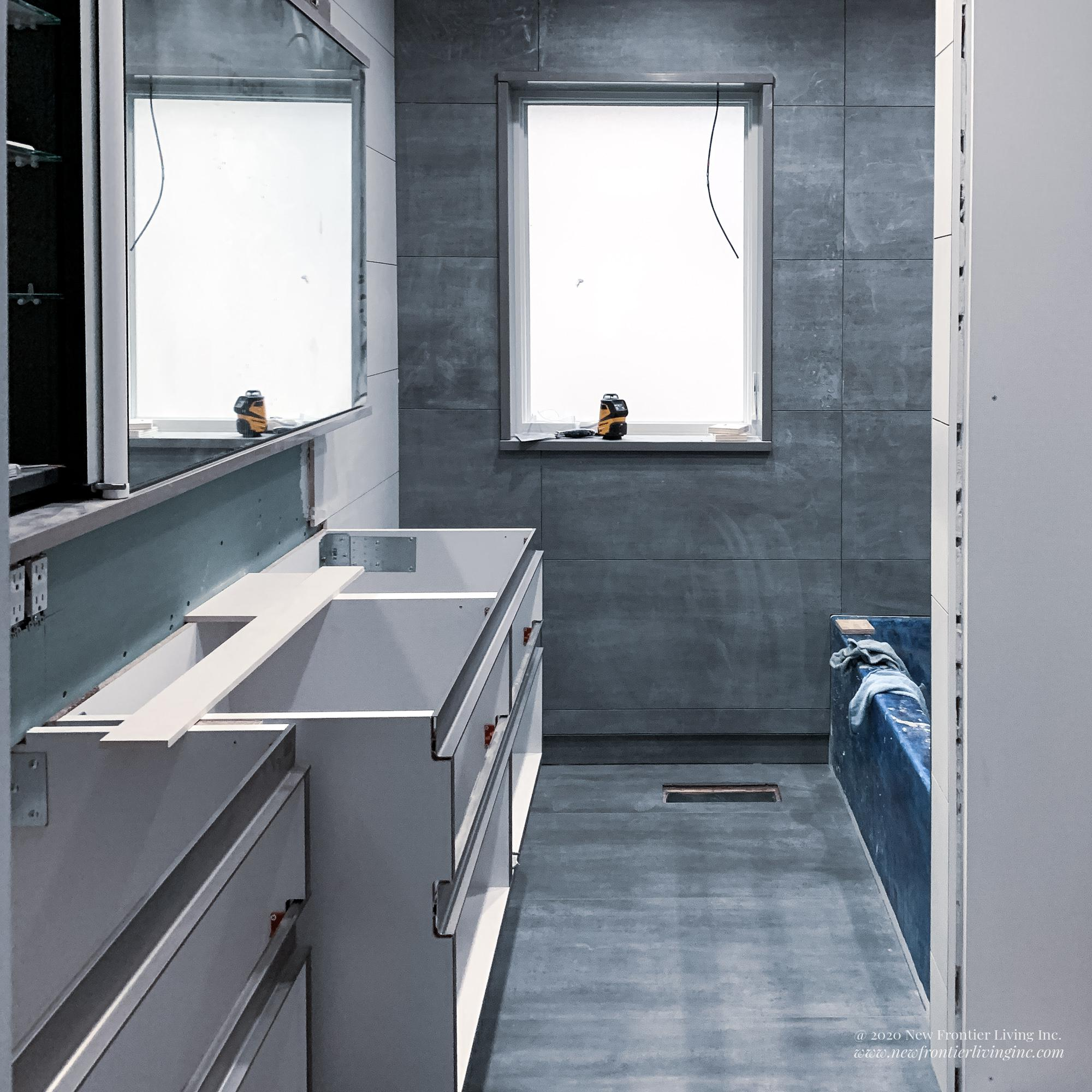Bathroom during remodeling, bare cabinetry boxes and tiles, blue protection on the tub