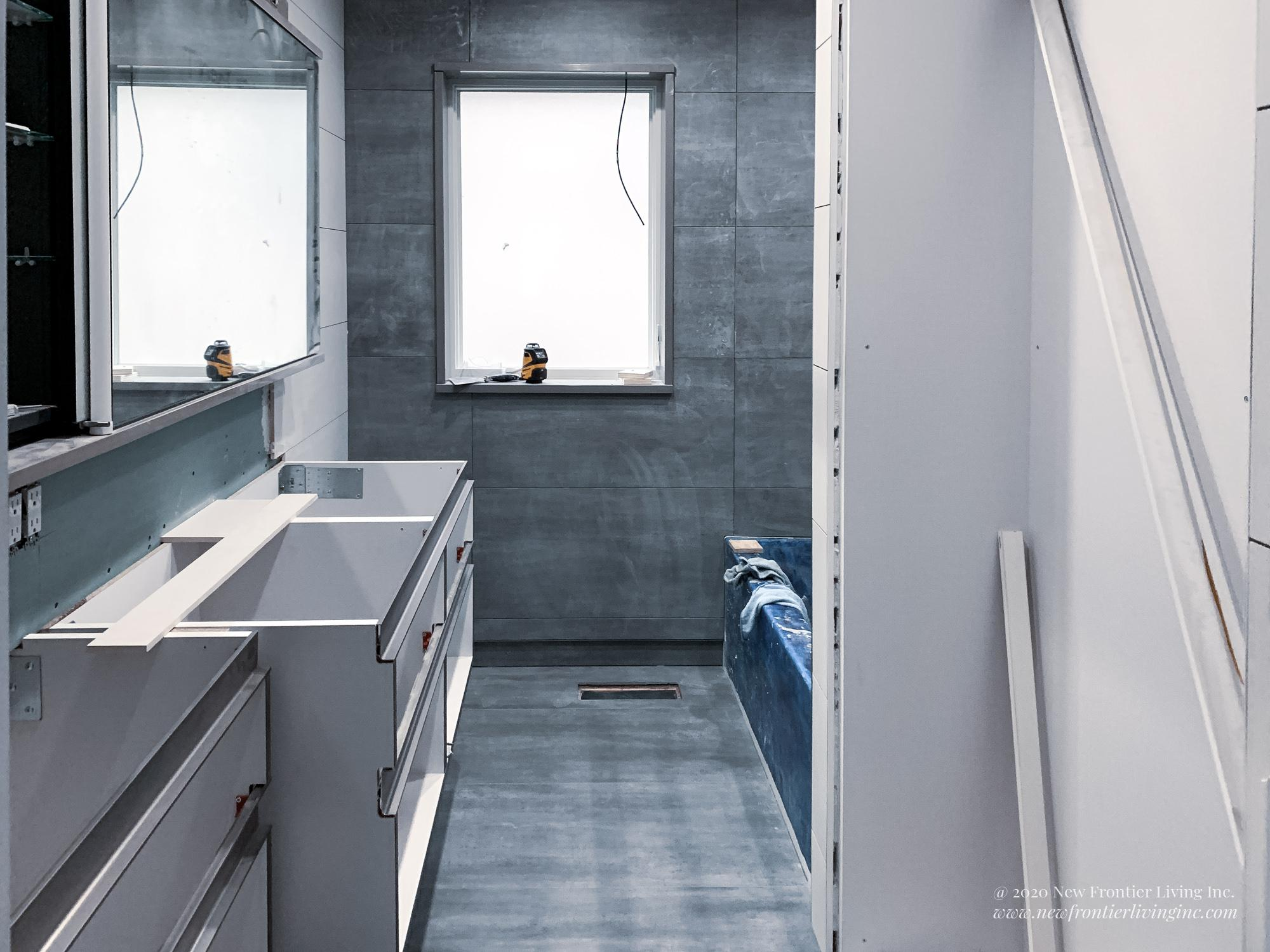 Bathroom during remodeling, bare cabinetry boxes and tiles, blue protection on the tub, drywall for linen cabinet