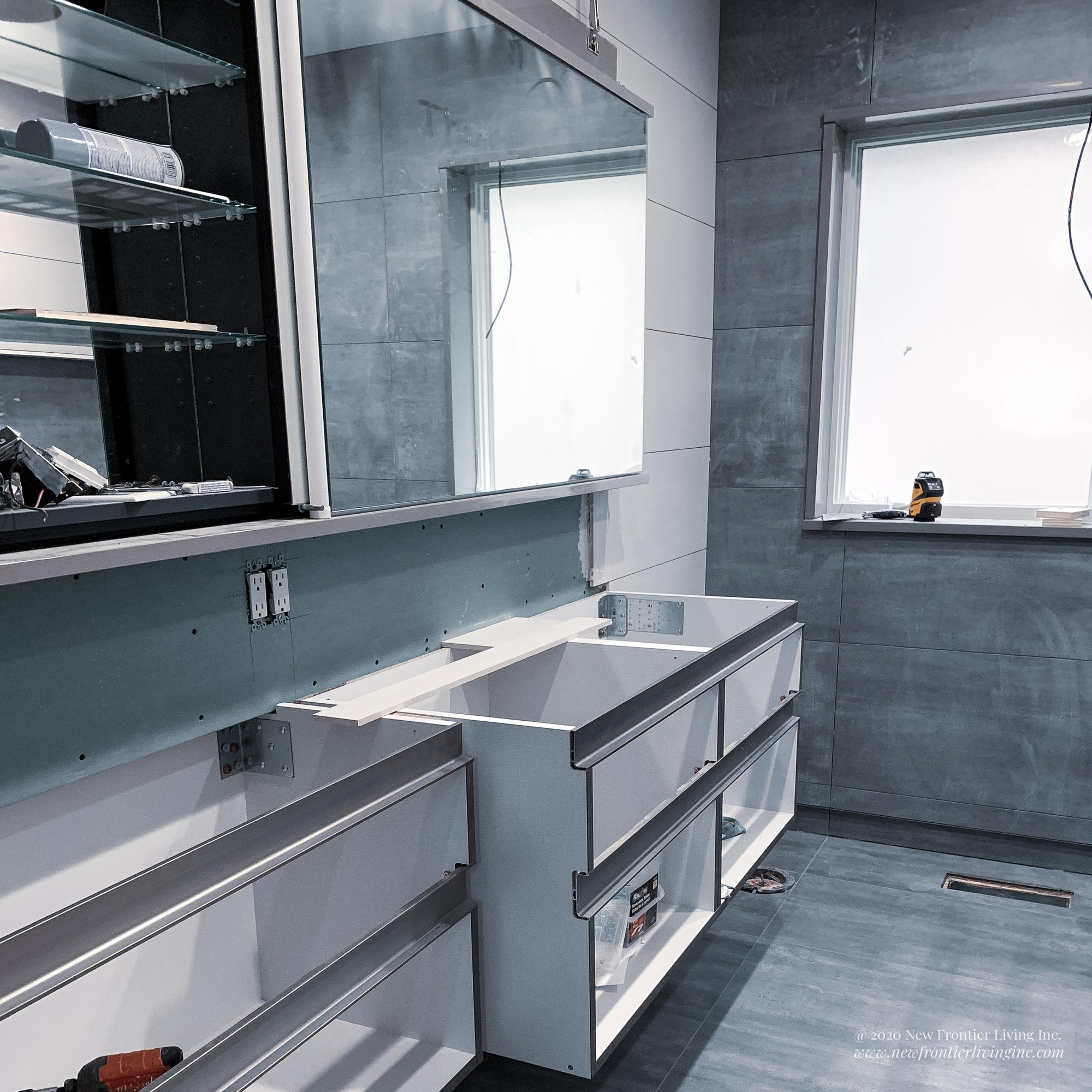 Bathroom during remodeling, bare cabinetry boxes and tiles