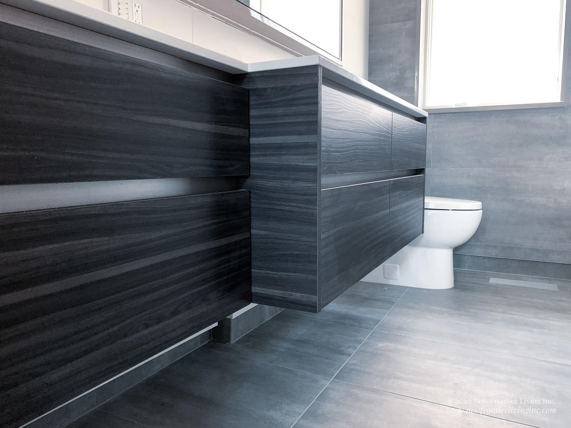 Small dark and light gray bathroom with white counters, tu