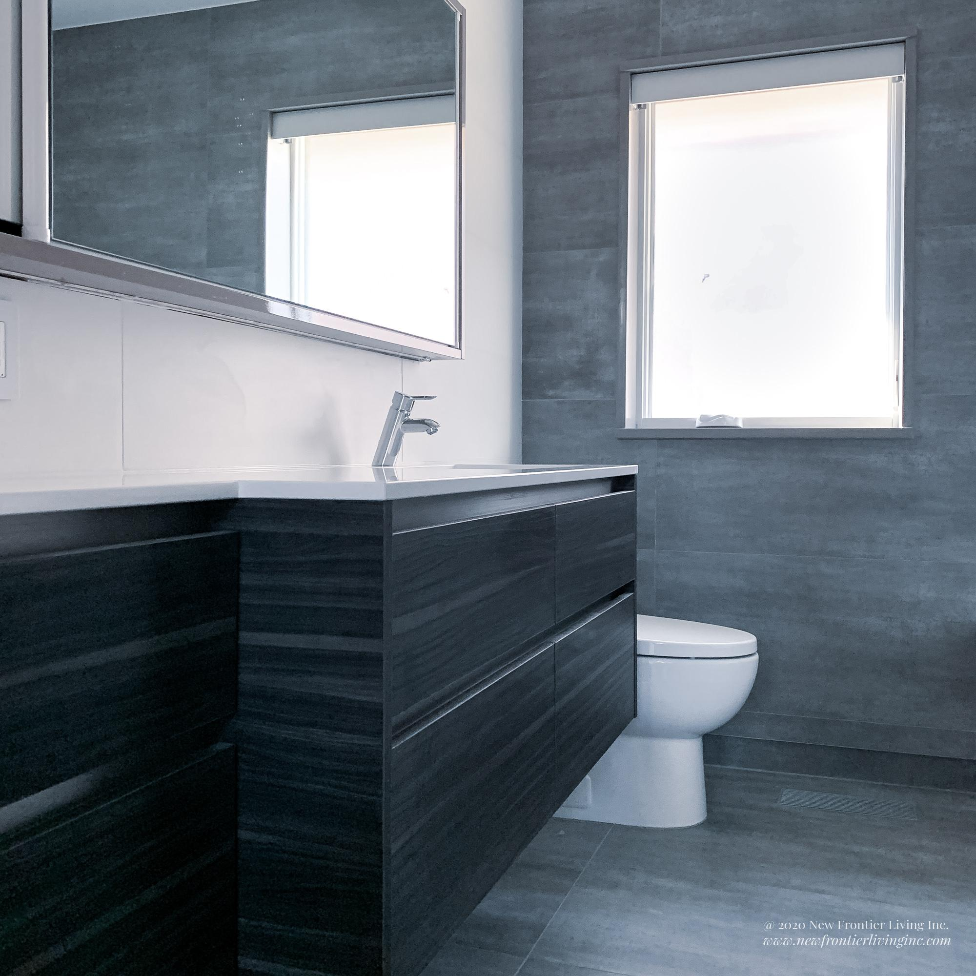 Small dark and light gray bathroom with white counters, tub and shower and single sink