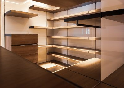 Light wood walk-in closet with multitude of shelves and drawers