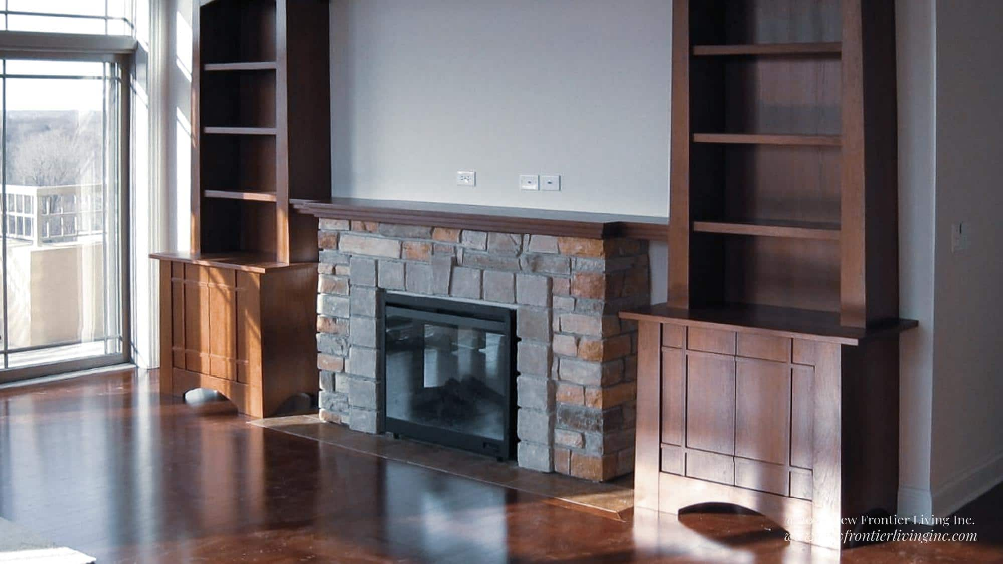 Stone brick fireplace with bookshelves on the sides and TV mount above